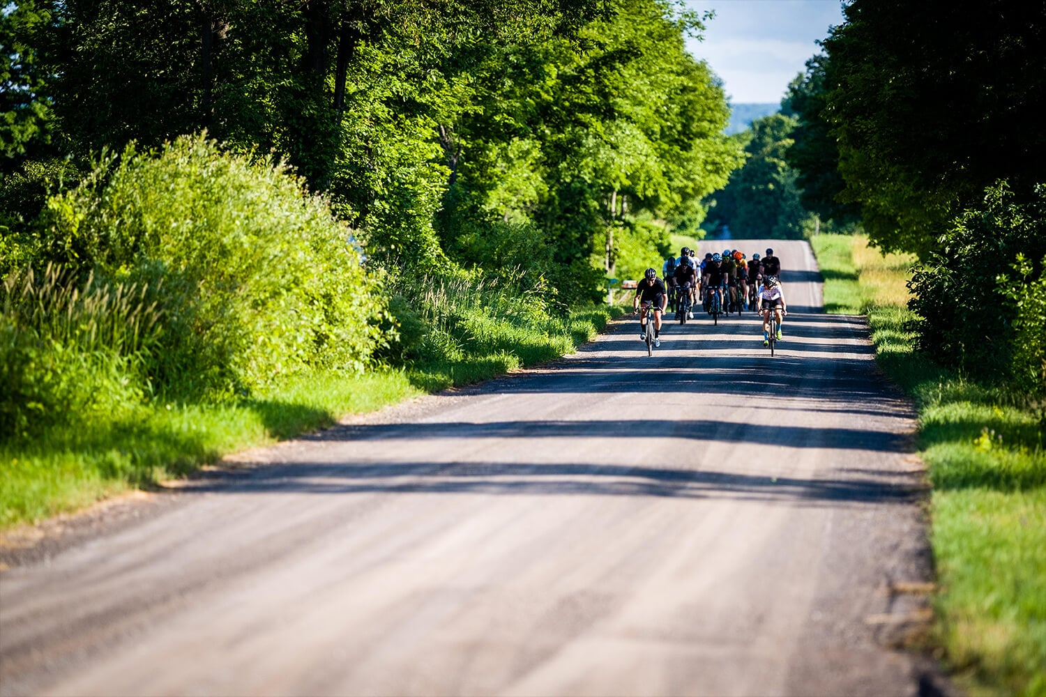 Group of gravel cyclist riding their Shimano GRX bikes down a dirt road
