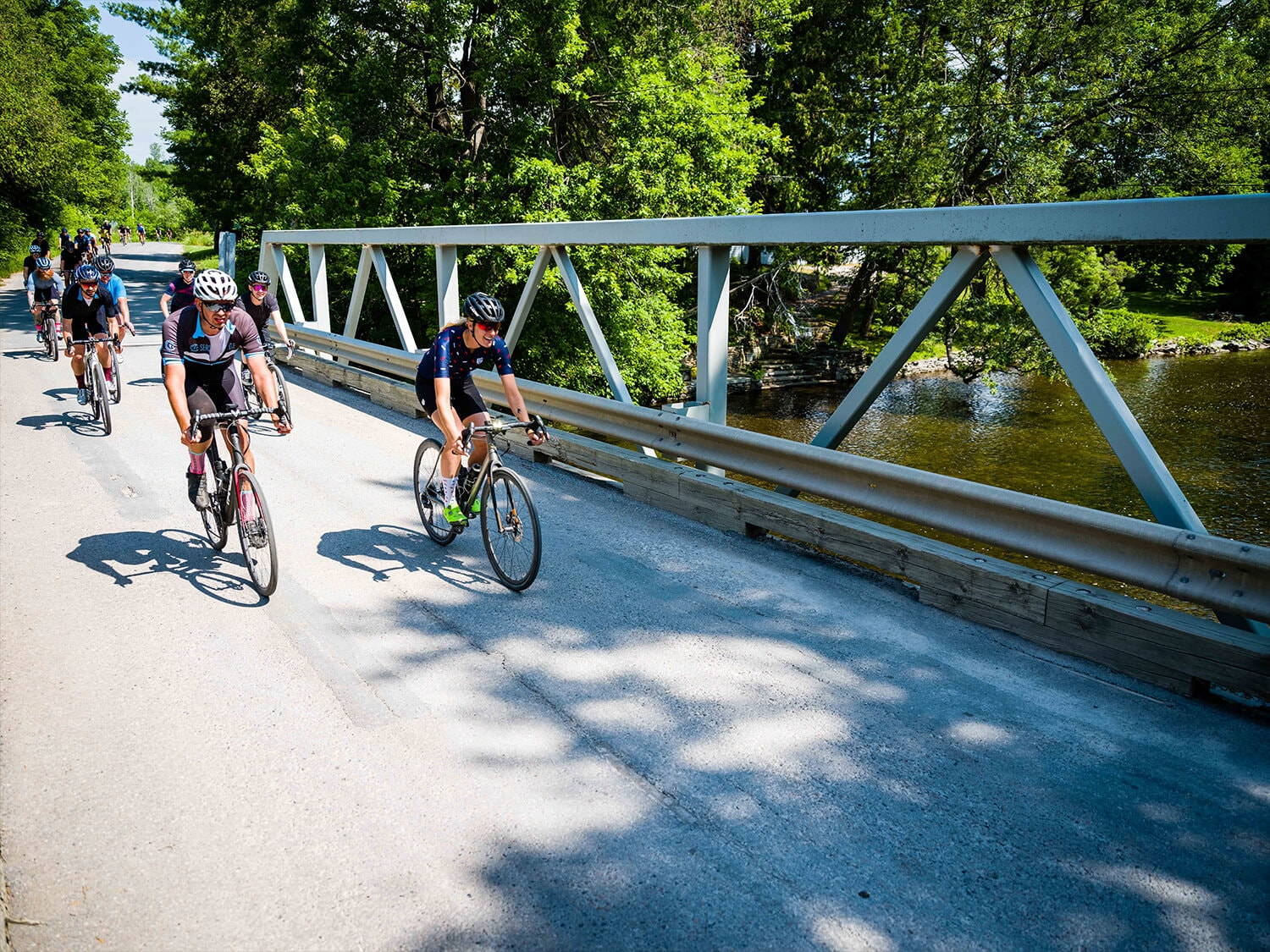 Road cyclist riding in a group across a bridge on their road bicycles with Shimano gears